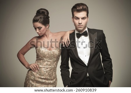 Handsome young elegant man looking at the camera with his hand in pockets while his lover is leaning on him and looking down. - stock photo