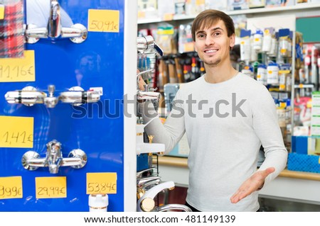Handsome young european man buying new water cock in supermarket
