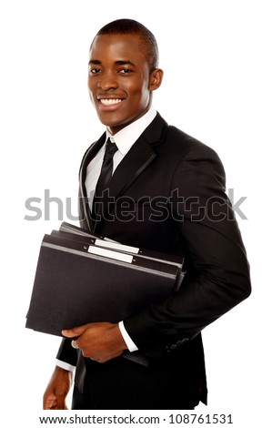 Handsome young executive holding files looking at camera