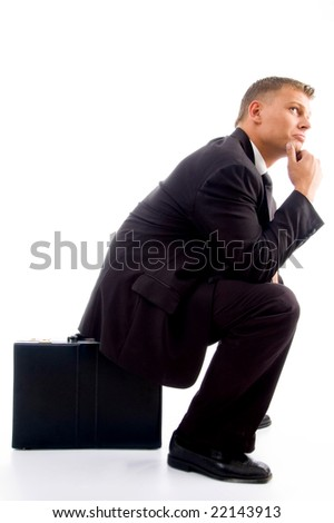 handsome young executive in deep thought sitting on his briefcase with white background - stock photo