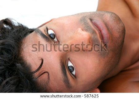 Handsome young exotic man, lying in bed - stock photo