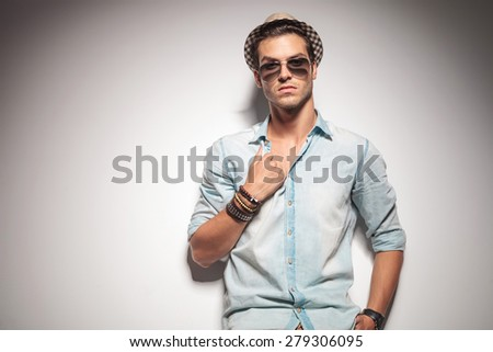 Handsome young fashion man leaning on a studio wall while pulling his shirt. - stock photo