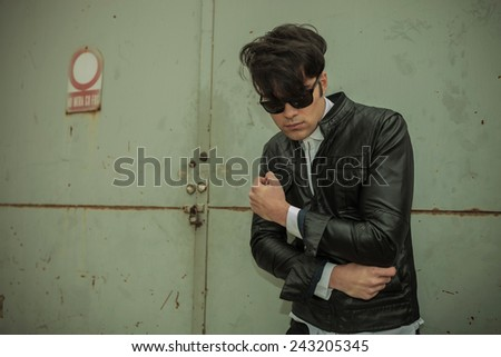 Handsome young fashion man looking down while fixing his jacket, near a metal gate.