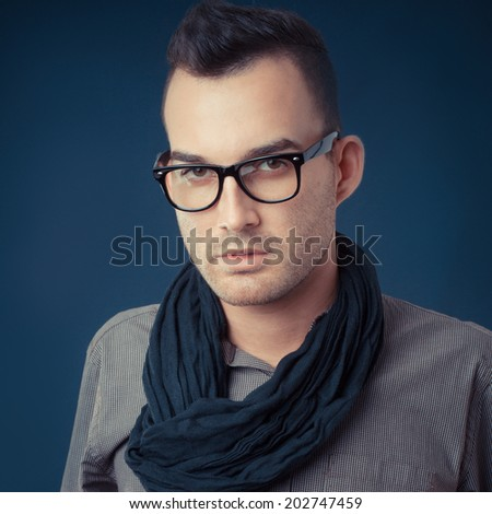 handsome young fashion man wearing scarf - shot in studio - stock photo