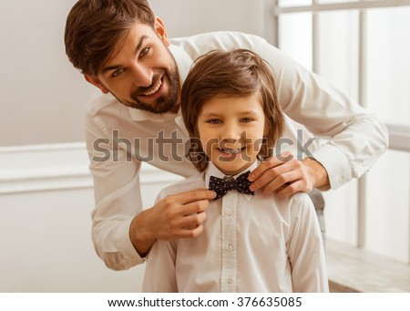 Handsome young father adjusting his cute little son's bow tie. Both white classical shirts looking in camera and smiling - stock photo