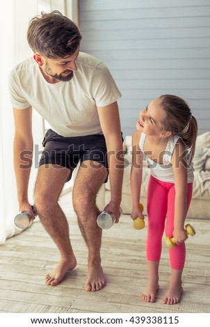 Handsome young father and his cute little daughter are looking at each other and smiling while working out with dumbbells at home - stock photo