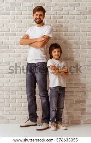 Handsome young father and his cute little son standing back to back, looking in camera and smiling. Both in white t-shirts and jeans, standing against white brick wall. - stock photo