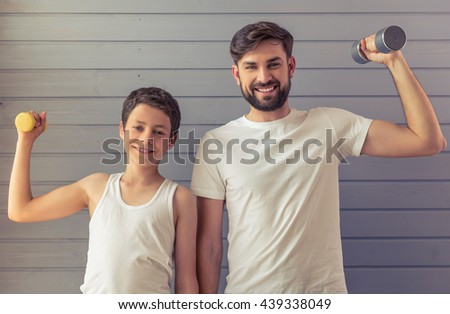Handsome young father and his teenage son are looking at camera and smiling while working out with dumbbells - stock photo