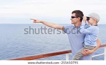 handsome young father holding his little son looking through binoculars, both enjoying cruise ship vacation together - stock photo