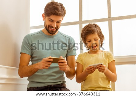 Handsome young father in casual clothes and his cute little son using smart phones while sitting near the window - stock photo