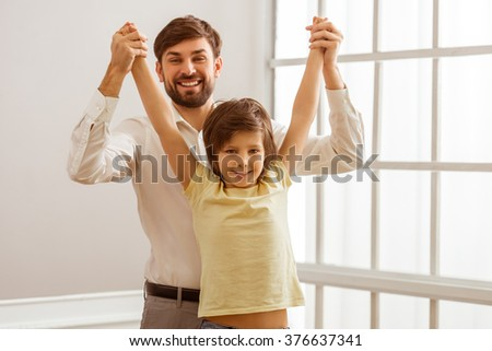 Handsome young father in classical clothes and his cute little son holding hands, looking in camera and smiling while standing in the room - stock photo