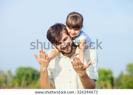 Handsome young father is standing and holding daughter on shoulders. They are playing in forest. The man and girl are holding hands and smiling