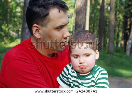 Handsome young father with little cute son sit in summer forest and think - stock photo