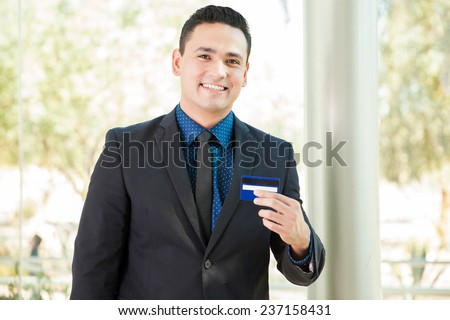 Handsome young financial adviser presenting a new credit card and smiling - stock photo