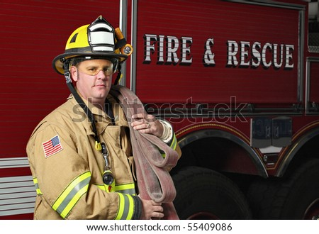 handsome young fireman holding fire hose in uniform in front of firetruck