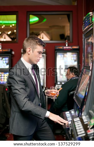 Handsome young gambling man on the slot machine in casino - stock photo