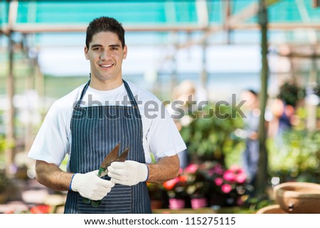 handsome young gardener portrait in greenhouse - stock photo
