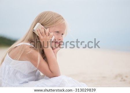 Handsome young girl talking on phone at the beach
