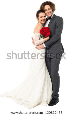 Handsome young groom embracing his darling wife, full length on white. - stock photo