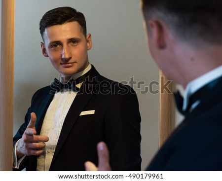 Handsome young  groom going to his wedding, wearing a suit and adjusting his shirt