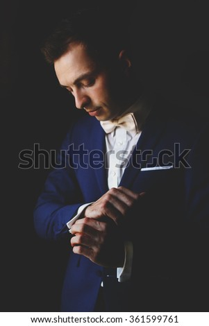 Handsome young  groom going to his wedding, wearing a suit and adjusting his shirt near the window - stock photo