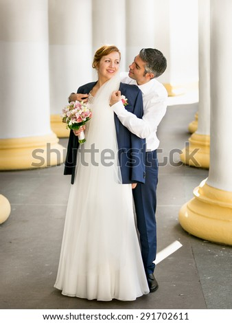 Handsome young groom hugging beautiful bride from back at ancient columns