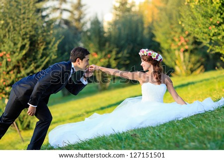 handsome young groom kissing beautiful bride and smiling - stock photo