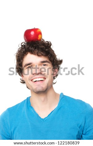 Handsome young guy balancing a red apple on his head. He is smiling and wearing a blue sweater. Isolated on white background - stock photo