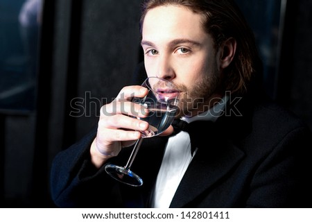 Handsome young guy drinking wine at business party. - stock photo