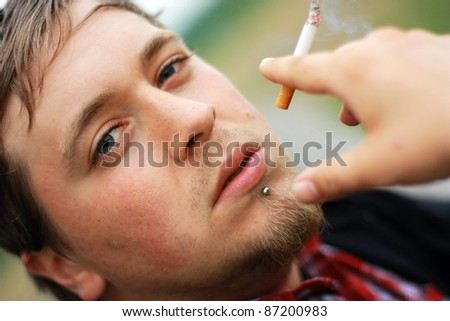 Handsome young guy smoking a cigarette