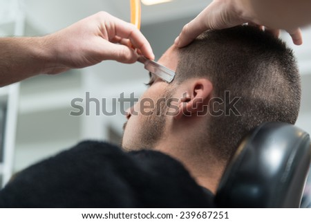 Handsome Young Hairdresser Giving A New Haircut To Male Customer At Parlor - stock photo