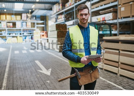 Handsome young handyman or warehouse supervisor standing amongst the building supplies with a tablet in his hand smiling at the camera - stock photo