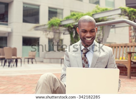 Handsome young happy businessman working on laptop computer outdoors on a background of corporate office building. Instagram filter effect