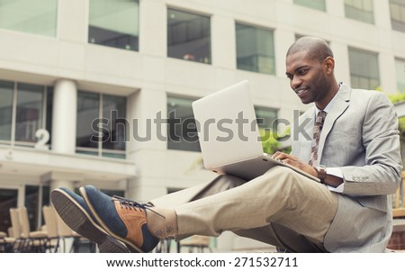 Handsome young happy businessman working on laptop outdoors on a background of corporate building. Instagram filter effect  - stock photo