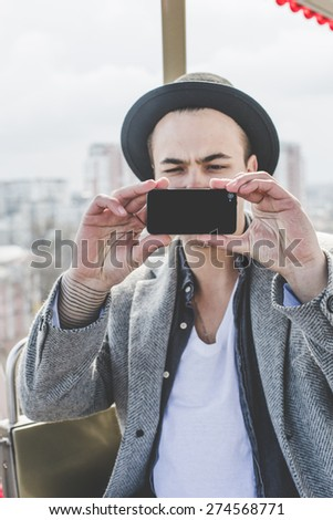 handsome young hipster guy in hat taking selfie with his smart phone in cabin of ferris wheel over city view from high background during sunny summer day on the festival - stock photo