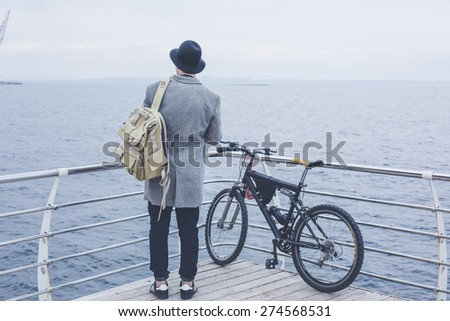 handsome young hipster guy in hat with bike looking at the sea wearing backpack on wood floor back view - stock photo