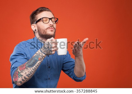 Handsome young hipster is enjoying aroma of coffee. He is holding a cup near his nose and waving his arm. The guy is standing and smiling. Isolated and copy space in right side - stock photo