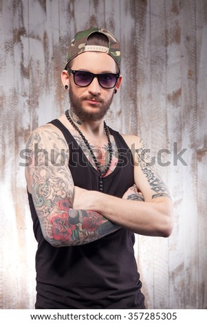Handsome young hipster with tattoo and beard. He is standing and crossing his arms. The man is standing and looking at camera confidently - stock photo