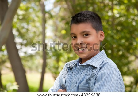 Handsome Young Hispanic Boy Having Fun in the Park. - stock photo