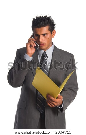 Handsome young Hispanic business man in a grey suit standing talking on his cell phone and looking into a file folder