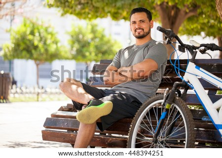 Handsome young Hispanic man ready to exercise on his bicycle around the city and smiling - stock photo