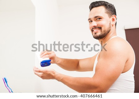 Handsome young Hispanic man with a beard putting on some moisturizing cream in the bathroom - stock photo