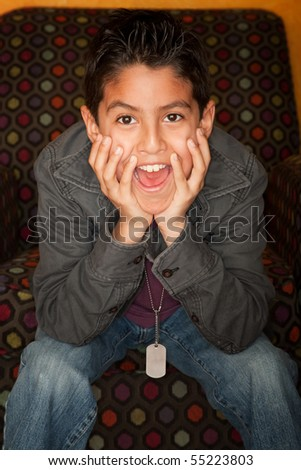 Handsome Young Hispanic Seated in Colorful  Chair - stock photo