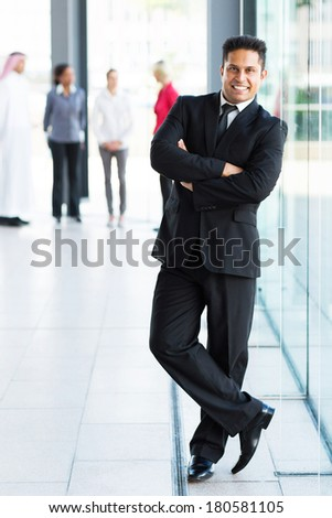 handsome young indian businessman with arms crossed - stock photo