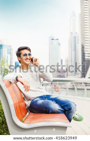handsome young indian man talking on phone on a street - stock photo