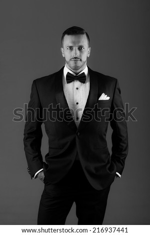 Handsome young latin man wearing a tuxedo black and white portrait - stock photo