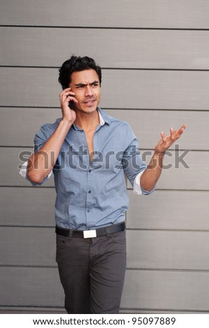 Handsome young latino professional businessman upset on phone