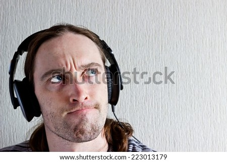 Handsome young long hair man with headphones thinking about music and looking up - stock photo