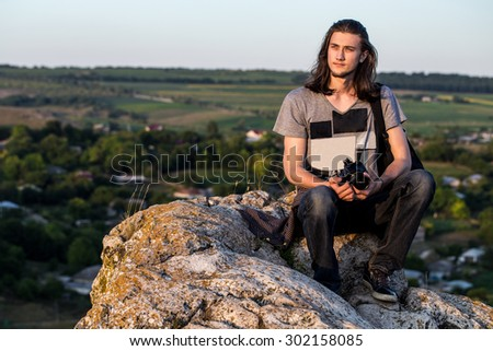 Handsome young longhair man sitting on a rocks with digital dslr camera against fields and blue background. Sunset shot. - stock photo