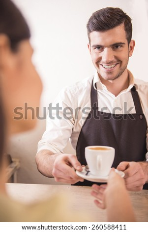 Handsome young male barista stretching out hand with cup of coffee and smiling. - stock photo